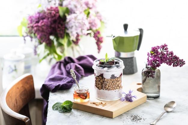 Granola fait maison dans un pot avec du yaourt grec et des mûres et des framboises sur la table avec du lilas.