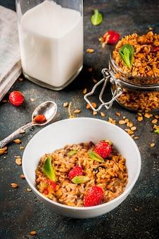 Granola fait maison à partir d'un mélange de céréales (orge, avoine, seigle, son) avec fraise, feuilles de menthe et lait frais bio