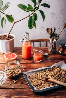 Granola fraîchement préparé sur plaque à pâtisserie et jus de pamplemousse sur table de cuisine