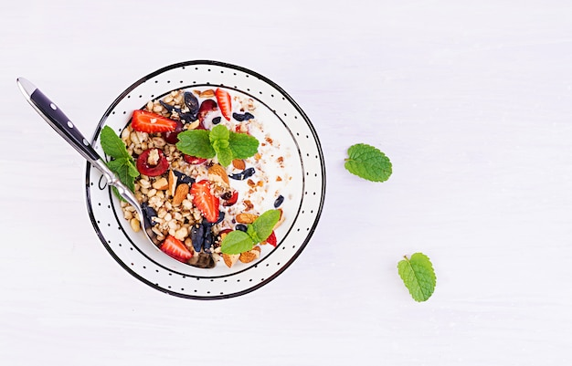 Granola, fraises, cerise, chèvrefeuille, noix et yaourt dans un bol