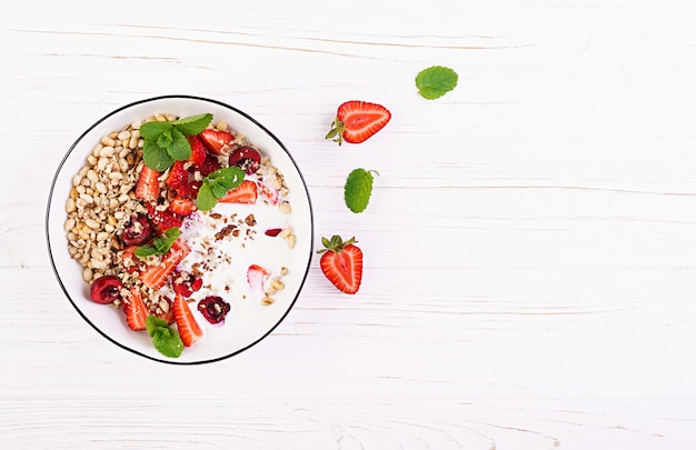 Granola, fraises, cerise, noix et yaourt dans un bol sur une table en bois