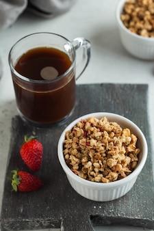 Granola maison dans un bol blanc avec des fraises et une tasse de café
