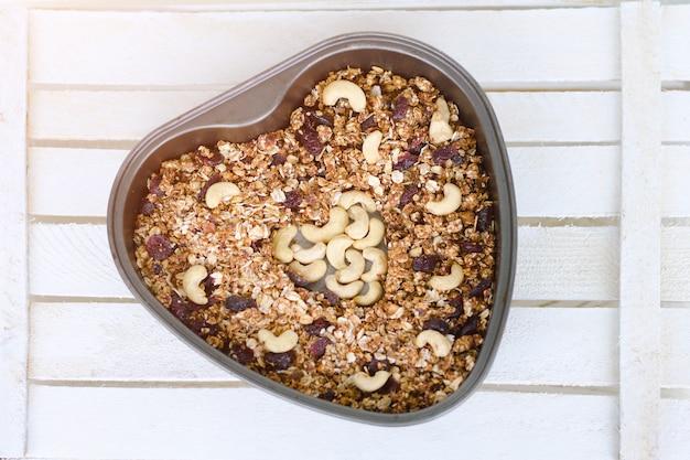 Granola sur une plaque en forme de coeur de cuisson