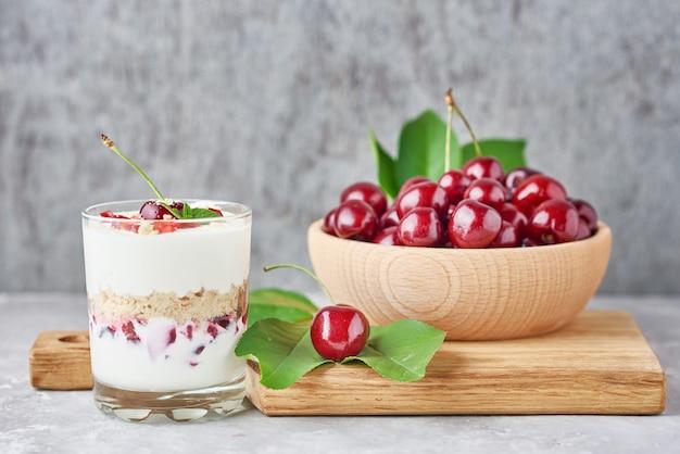 Granola ou yaourt avec cerise en verre, baies fraîches et pot de sucre sur une planche à découper, vue du dessus
