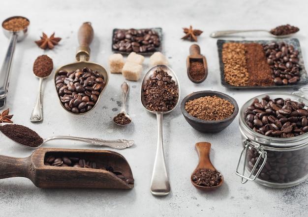 Granulés de café instantané lyophilisés avec café moulu et grains en plaque d'acier avec bocal en verre et diverses cuillères et boules sur fond blanc.