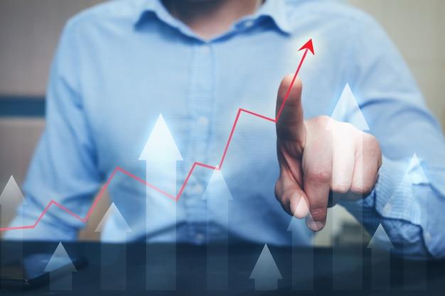 Graphe de flèche pointant le doigt d'homme d'affaires avec graphique.