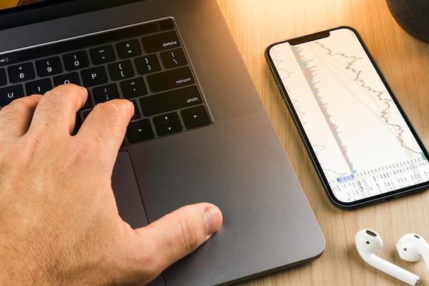 Graphique boursier financier sur l'écran du smartphone sur fond en bois avec un ordinateur à côté. bourse.