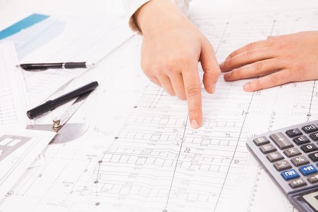 Graphique de construction sur fond de mains d'homme d'affaires avec des stylos blancs