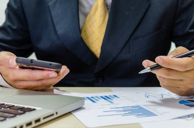 Graphique de document de l'homme d'affaires financier analysant et vérifiant les revenus-dépenses.