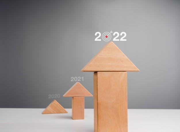 Graphique d'entreprise s'élevant jusqu'à l'année 2022. blocs de bois s'empilant comme des moyennes de flèche vers le haut sous forme de graphique de croissance avec icône cible sur fond blanc, style minimal et éco.