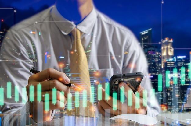 Graphique financier à double exposition et homme d'affaires à l'aide d'un smartphone et d'un stylo avec paysage urbain