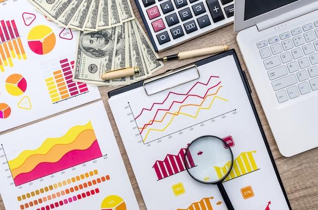 Graphique, loupe, dollar, calculatrice et ordinateur portable