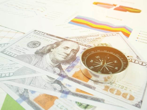 Graphique de rapport commercial et analyse de graphique financier avec dollar et boussole sur table