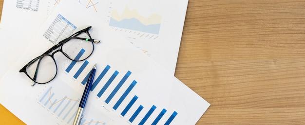 Graphique de statistiques et de tableaux de rapport de synthèse avec stylo et lunettes sur une table en bois pour montrer les bénéfices de la société lors de la réunion.
