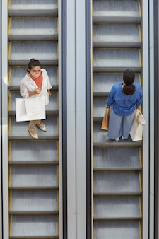 Graphique vue de haut en bas à deux femmes équitation escalator dans des directions opposées tout en faisant du shopping dans un centre commercial, se concentrer sur une femme portant un masque regardant la caméra, copiez l'espace