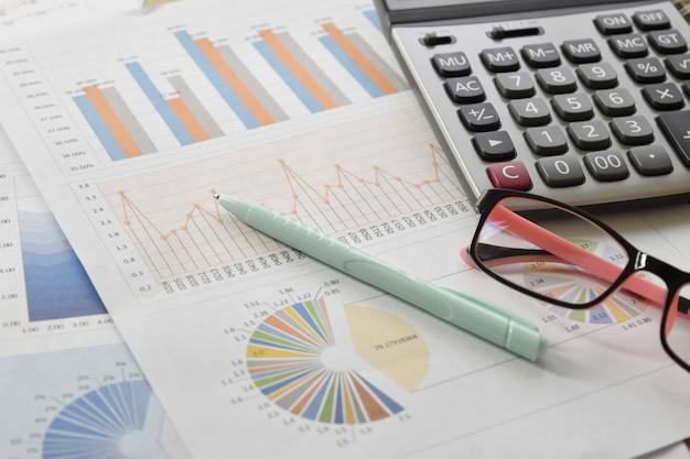Des graphiques financiers et des tableaux avec des lunettes, calculatrice sur le bureau.