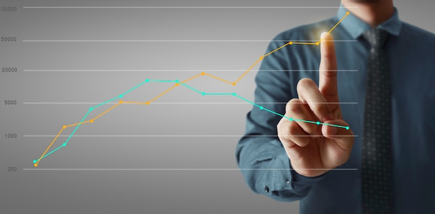 Graphiques touchant la main de l'indicateur financier et tableau d'analyse de l'économie de marché comptable