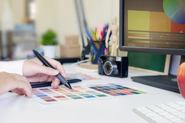 Graphiste agrandi à l'aide de tablette numérique et ordinateur au bureau.