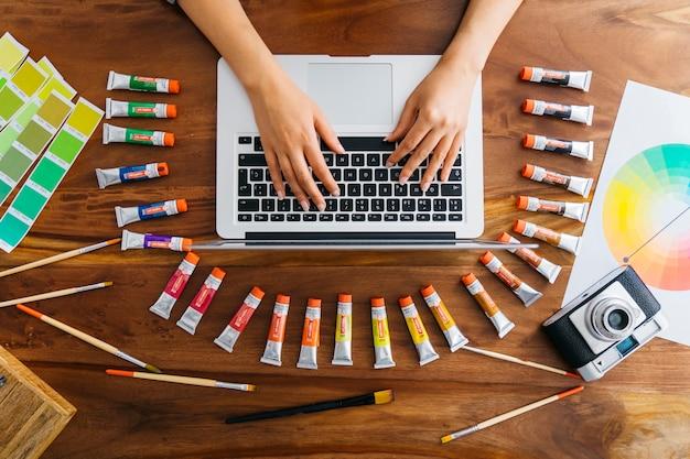 Graphiste chez ordinateur portable avec des matériaux de peinture