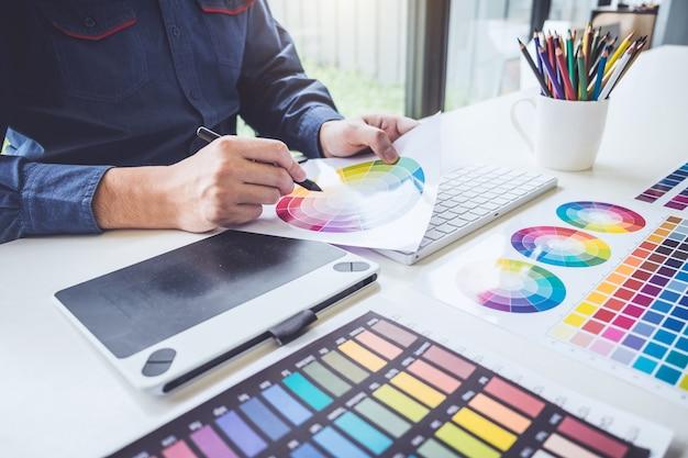 Graphiste créatif travaillant sur la sélection des couleurs et dessinant sur une tablette graphique au lieu de travail