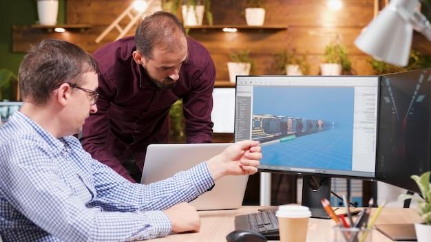 Graphiste dans l'industrie du jeu assis à son bureau discutant du graphisme du jeu vidéo