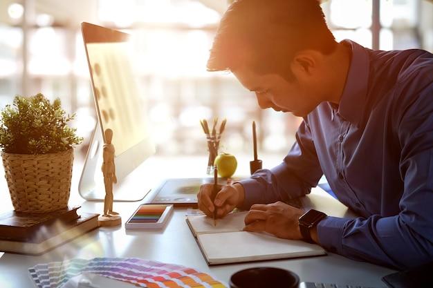 Graphiste dessinant sur un cahier