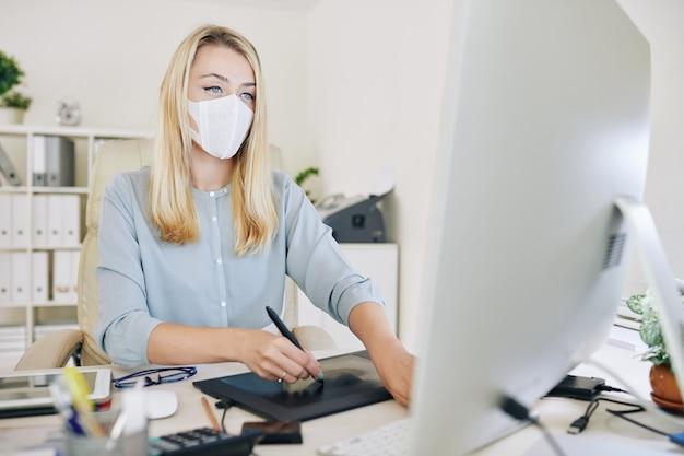 Graphiste femme avec masque médical