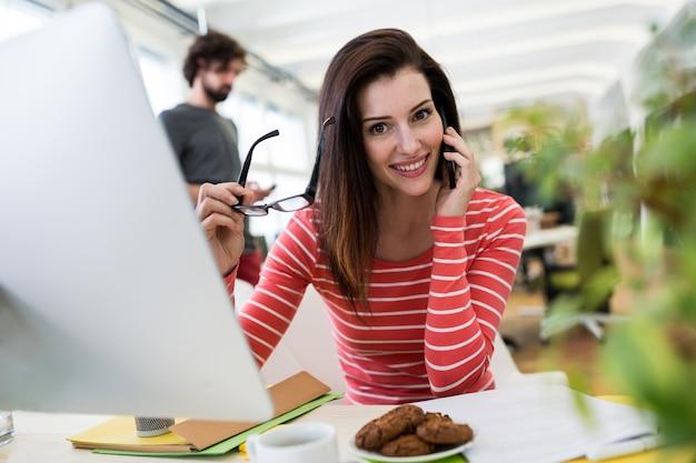 Graphiste femme parlant au téléphone mobile
