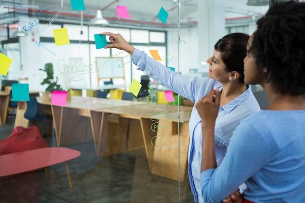 Graphiste femme pointant sur les notes autocollantes sur le verre au bureau de création