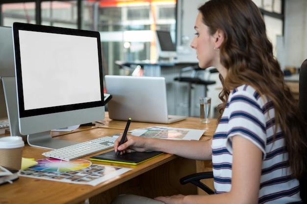 Graphiste femme utilisant une tablette graphique au bureau