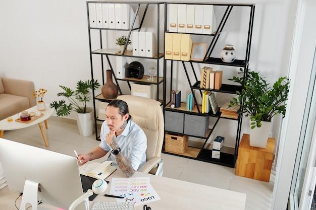 Graphiste freelance sérieux fronçant les sourcils travaillant sur ordinateur à table dans son bureau à domicile
