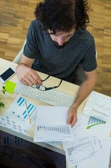 Graphiste homme regardant document graphique