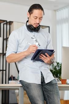 Graphiste professionnel pensif avec des écouteurs autour de son cou s'appuyant sur le bureau et dessin sur tablette numérique