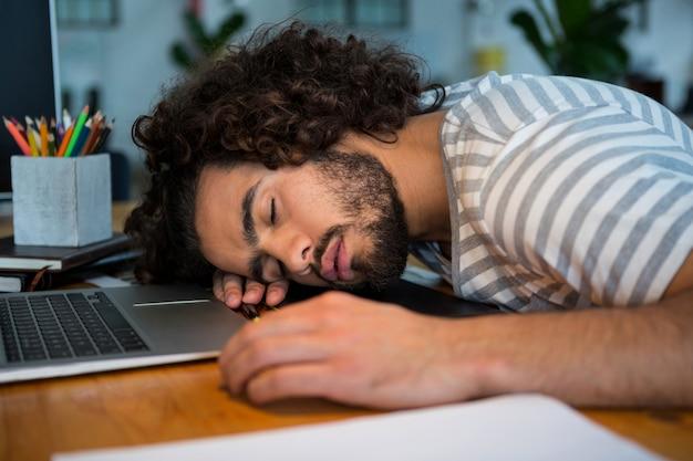 Graphiste surmené dormant sur son bureau