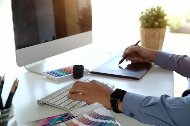 Graphiste travaillant sur un ordinateur de bureau moderne tout en utilisant une tablette graphique