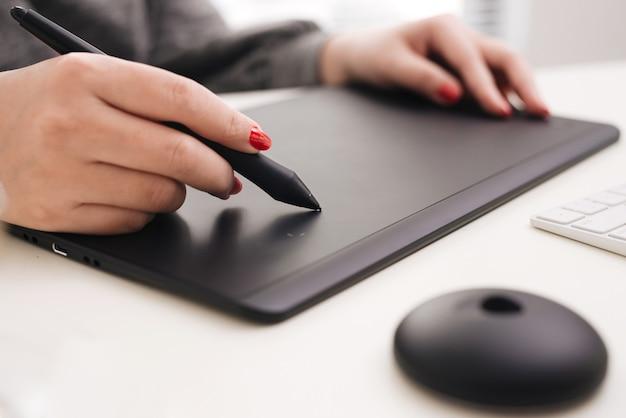 Graphiste travaillant avec une tablette de dessin numérique au bureau.