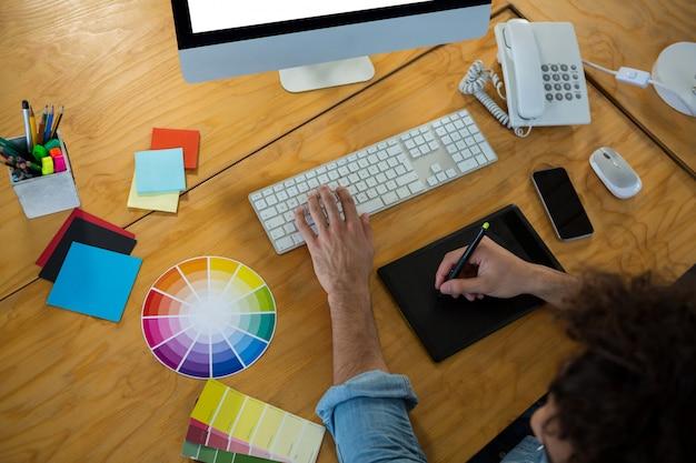 Graphiste utilisant une tablette graphique et un bureau