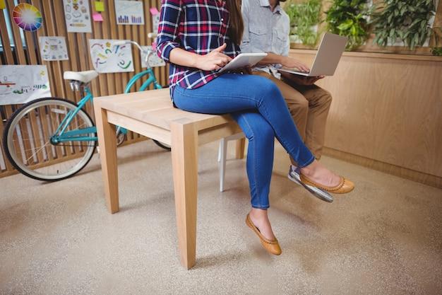 Graphistes assis sur un bureau à l'aide d'un ordinateur portable et d'une tablette numérique