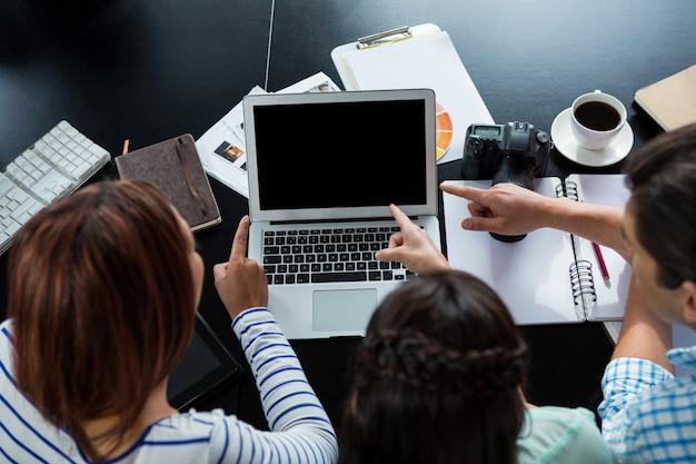 Graphistes discutant sur ordinateur portable