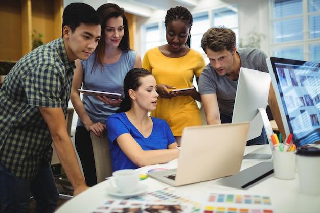 Graphistes discuter sur ordinateur portable