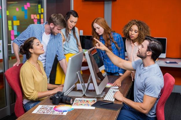 Les graphistes interagissent les uns avec les autres tout en travaillant au bureau