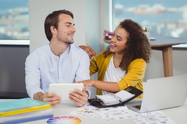 Graphistes souriants assis à table et utilisant une tablette numérique