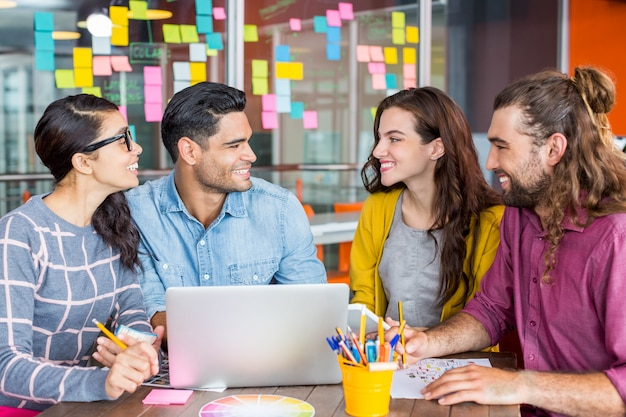 Graphistes souriants discutant sur ordinateur portable en réunion