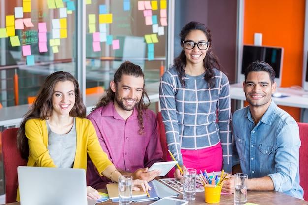 Graphistes souriants discutant sur tablette numérique en réunion