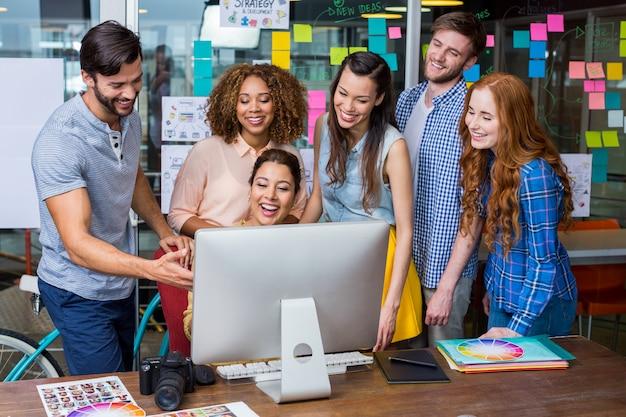 Graphistes souriants interagissant les uns avec les autres tout en travaillant au bureau