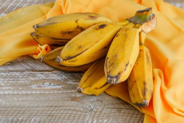 Grappe de banane vue grand angle sur bois et textile