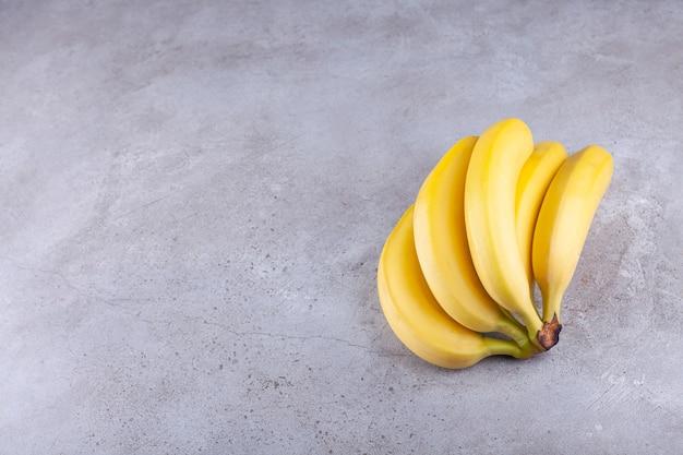Grappe de bananes jaunes mûres placées sur fond de pierre.