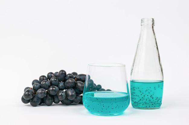 Une grappe de raisin, une bouteille et un verre avec un cocktail aux graines de basilic sur une surface légère
