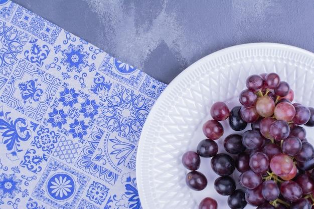 Une grappe de raisin dans une assiette blanche sur une table bleue.