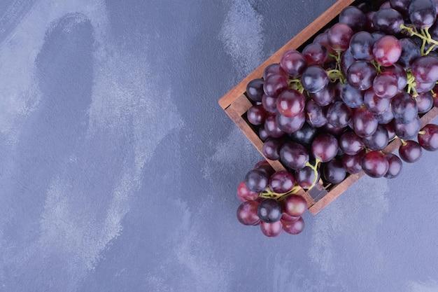 Une grappe de raisin dans un plateau en bois.